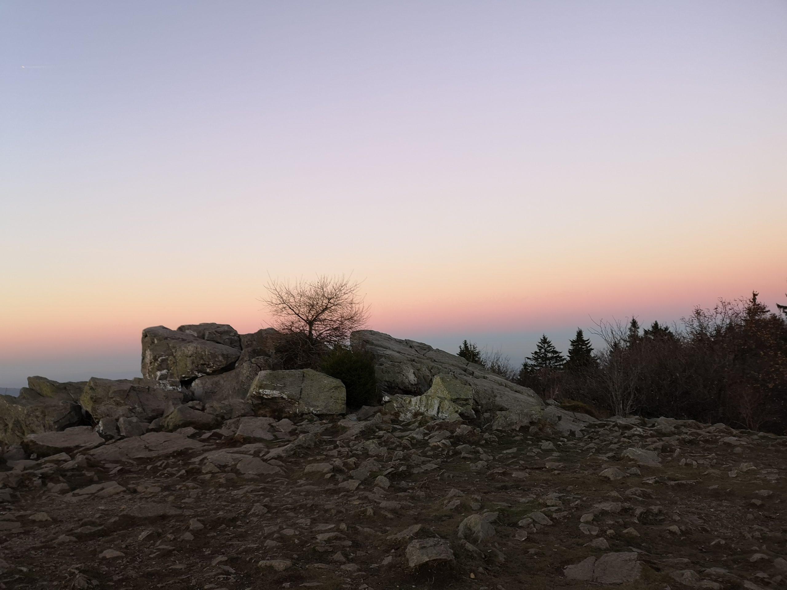 Sonnenuntergang in rosa und lila auf einem Berg im Wald. Metapher für den steilen Weg des Escorts und die schönen Abende die man verbringt